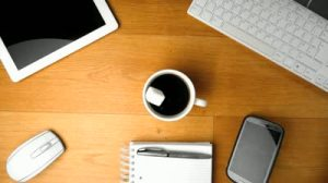 stock-footage-sugar-cube-falling-into-cup-of-coffee-next-to-tablet-pc-and-smartphone-keyboard-and-mouse-in-slow